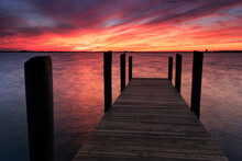 A Fiery Sunset Casts A Glow Over A Fishing Pier On South Hutchinson Island, Florida