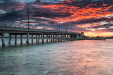 A Fiery Sunset Looms Over A Drawbridge Spanning The Indian River At North Hutchinson Island, Florida