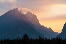 The Cathedral Group Of Tetons And Cascade Canyon Are Blanketed In A Colorful Haze Of Forest Fire Smoke At Sunset In Grand Teton National Park, Wyoming.