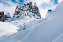 A Snowboarder Makes A Turn In Fluffy Powder In Cinque Torri, Cortina, In The Italian Dolomites