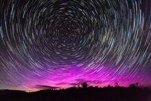 Stars Swirl Around Polaris, The North Star, As Northern Lights Dance On The Northern Horizon Over Jackson Hole, Wyoming.