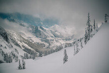 Skier Makes Some Steep Angle Powder Turns In The Cascades Of Washington As A Snow Storm Begins To Clear.