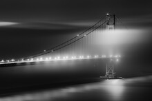 Black And White View Of The Golden Gate Bridge At Night With Silky Low Fog Around The Tower.