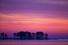 Scenic Of Trees And Water At Dawn On A Peninsula Against A The Pink And Purple Sky Just Before Sunrise In Chesapeake Bay, Tighlman Island, MD.