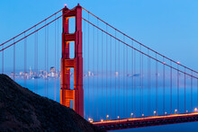 With The San Francisco Bay Full Of Beautiful Low Lying Fog, The Commuting Traffic Glows Across The Golden Gate Bridge.