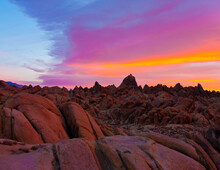 Alabama Hills, Lone Pine, CA: Brilliantly-colored Pre-dawn Sky Casts A Rosy Glow Over Foreground Boulder Field And Background Low Peaks.
