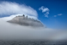 Faroe Islands. The Islet Of Tindholmur Peeks Out Of The Fog And Mist.