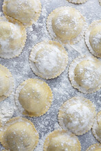Food Photography Of A Stainless Steel Kitchen Baking Tray With Fresh, Uncooked Tortellini Pasta Dusted With Flour.