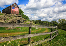 Old Barn In CT On A Rock Outcrop With An American Flag On Its Facade