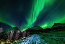Nordlichter In Troms, Nordnorwegen. Tanzende Aurora Borealis In Grün, Pink Und Weiss. Wundervolles Naturerlebnis Im Hohen Norden In Einer Klaren Und Kalten Winternacht In Den Lyngenalps.