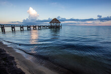 Just Before Sunrise, A Long Empty Wooden Dock Juts Out Into The Caribbean Sea.