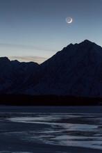 Waxing Crescent Moon Setting Over Teton Mountains And Jackson Lake, Grand Teton National Park, Wyoming