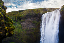 A Rock Formation Which Looks Like A Troll's Head Overlooks Skogafoss, A Waterfall In Southern Iceland.