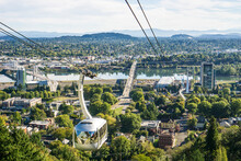 The Ariel Tram Makes Its Way From Campus To The City's Waterfront Below. Snow-capped Mount Hood Can Be Seen In The Distance.