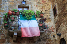 Patriotic Display Of The Italian Flag From A Balcony In The Medieval Walled City Of Pienza, Tuscany