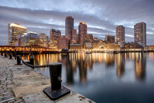 The Lights Of Downtown Reflect On The Waters Of The Fort Point Channel At Sunset In Boston, MA.