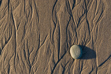 Flowing Water Creates Intricate Patterns In The Sand On A Southern California Beach.
