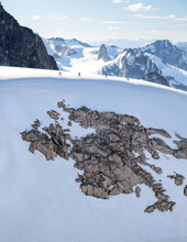 A Group Of Climbers Trek Across The Glacier Ridge Line After Descending From The Becky-Chouinard Route On The Howser Towers In Bugaboos, British Columbia, Canada
