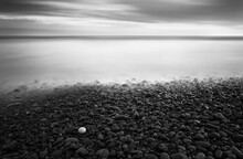 A Black And White Image Of One Yellow Pebble That Stands Out Against All Other Black And Grey Pebbles In A Fine Art Long Exposure Of The Ocean And Clouds.