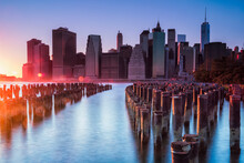 Sunset Illuminates The Skyscrapers Of Lower Manhattan And Pilings In The East River North Of Pier 2 In Brooklyn Bridge Park, New York City