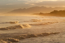 Early Light Hits The Waves Crashing On The Shores Of Palma Real, Honduras, With The Tropical Mountains Of Pico Bonito National Park Looming In The Distance.