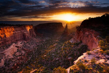 The Sun Rises Above Independence Monument Of Colorado National Monument Near Grand Junction, Colorado.