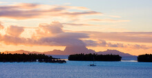 French Polynesia: Three Small Islets With Main Island In Background At Sunset With Orange And Purple Clouds