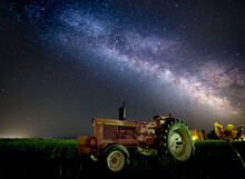 A Pink Tractor (with A Breast-cancer Awareness Ribbon) Sits Beneath The Milky Way In A Tulip Field.