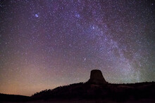 The Milky Way Galaxy Stretches Above Devil's Tower In Devil's Tower National Monument, Wyoming.