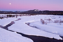 A Near-full Moon Hovers Above Pacific Creek And The Absaroka Mountains In Grand Teton National Park, Wyoming.