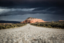 Rock Formations In Monticello, Utah Painted With Light During An On Coming Desert Storm As Seen From A Country Road