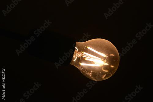 Obraz Stara i brudna  żarówka elektryczna słabo świeci żółtym światłem.  - fototapety do salonu