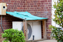 An Outdoor Air Conditioner AC Unit Placed On The Ground At A Garden Within A Small Protective Utility Shed With Corrugated Painted Metal Roof. This Provides Weather Protection For The Electrical Unit.