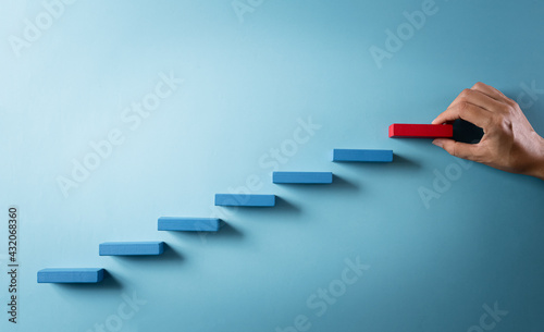 Concept of building success foundation. Hand holding wooden block stacking as step stair, Success in business growth concept on pastel background.