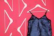 Leinwandbild Motiv Women's garment and hangers on pink background, flat lay. Clothes rent concept