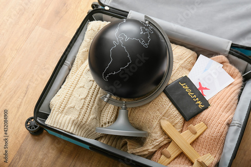 Globe with wooden airplane, passport and tickets in packed suitcase on wooden background - fototapety na wymiar
