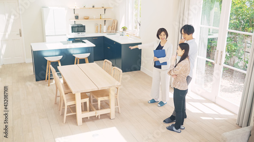 カップルに部屋を案内する女性担当者 モデルハウス ハウスメーカー 部屋探し