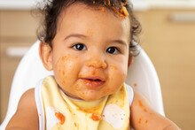 Close Up Portrait Of Baby In High Chair With Messy Face