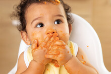 Close Up Portrait Of Funny Baby In High Chair With Guilty Messy Face
