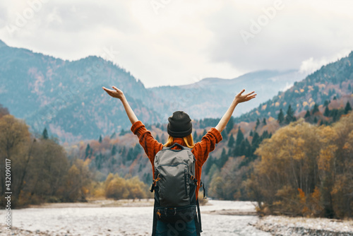 woman in a jeans sweater with a backpack travels in the mountains on nature in autumn - fototapety na wymiar