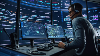 Professional IT Technical Support Specialist and Software Developer Working on Computer in Monitoring Control Room with Digital Screens. Employee Wears Headphones with Mic and Talking on a Call.