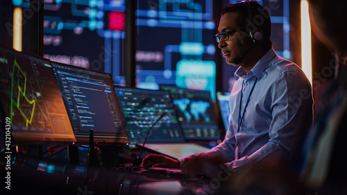 Professional IT Technical Support Specialist and Software Developer Working on Computer in Monitoring Control Room with Digital Screens. Employee Uses Headphones with Mic, Talking on a Call.