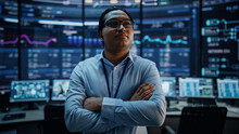 Portrait Of Professional Indian IT Technical Support Specialist Or Software Developer Crossing Arms On Camera In A Modern Monitoring Control Room Full Of Computer Displays With Technological Data.