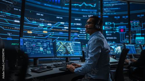Professional IT Technical Support Specialist and Software Developer Working on Computer in Monitoring Control Room with Digital Screens. Employee Uses Headphones with Mic and Talking on a Call.