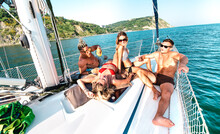 Young Rich Friends Chilling On Sailboat At Sea Trip - Guys And Girls Having Summer Fun Together At Sail Boat Party Day - Luxury Excursion Concept On Warm Vivid Filter