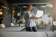 Businessperson Lifting Opened Laptop While Staying At Her Desk