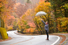 Woman Standing In The Middle Of The Road Holding An Umbrella, Honshu, Japan