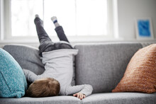 Cute Child Lying Face Down On The Sofa