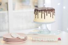 Vanilla Birthday Cake With Chocolate Ganache, Glaze,  On A Cake Stand In A  Kitchen