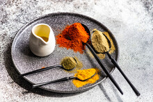 Spoonfuls Of Multi Coloured Spices On A Plate With A Jug Of Olive Oil
